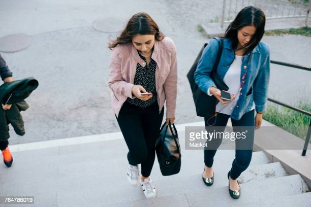 High angle view of female friends moving up on staircase while using smart phones
