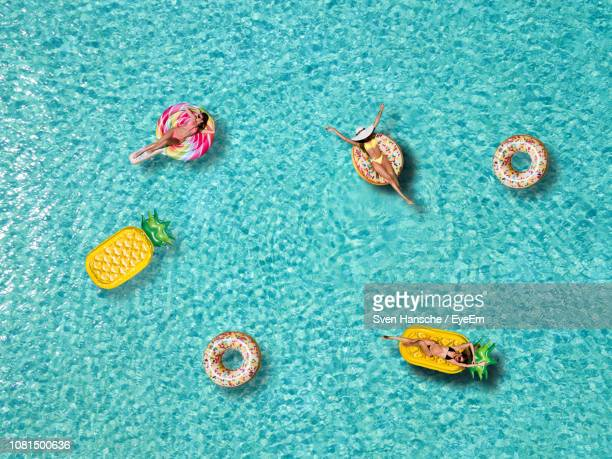 high angle view of female friends relaxing on pool rafts in sea - inflatable stock pictures, royalty-free photos & images