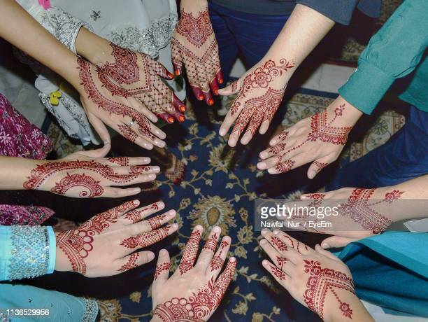 High Angle View Of Female Friends Showing Henna Tattoos At Home