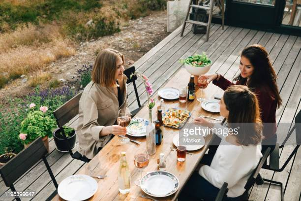 high angle view of female friends talking while enjoying meal at front yard - tre persone foto e immagini stock