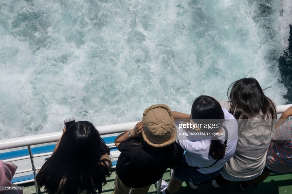 High Angle View Of Female Friends Traveling On Boat At Sea : Stock Photo