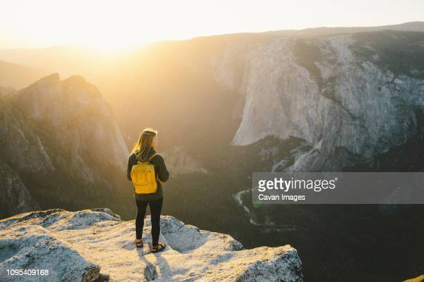 high angle view of female hiker standing on cliff at yosemite national park - national park stock pictures, royalty-free photos & images