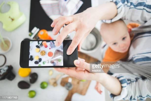 high angle view of female influencer food blogging with baby girl in kitchen - mensagem com foto imagens e fotografias de stock