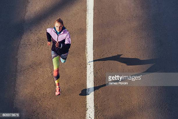 High angle view of female runner running on city road