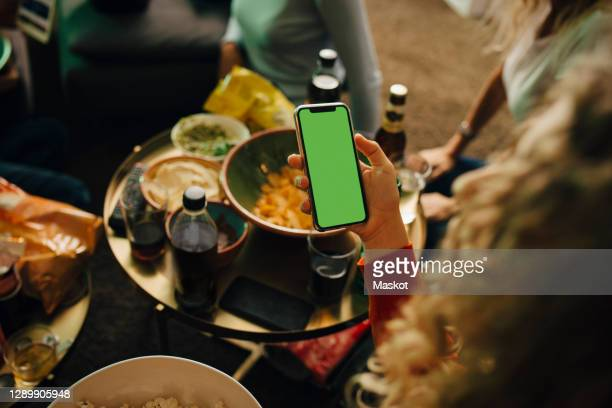high angle view of female sports fan using smart phone in living room - supporter stock pictures, royalty-free photos & images