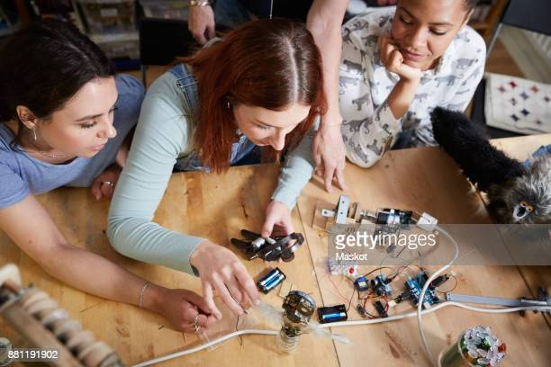 high angle view of female technicians making robot at table in workshop - inventor stock pictures, royalty-free photos & images