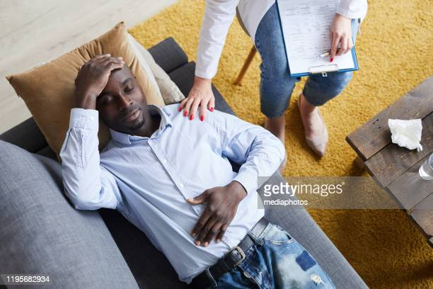 high angle view of female therapist with clipboard on knees touching shoulder of black patient while comforting him at therapy session - psychiatrist's couch stock pictures, royalty-free photos & images