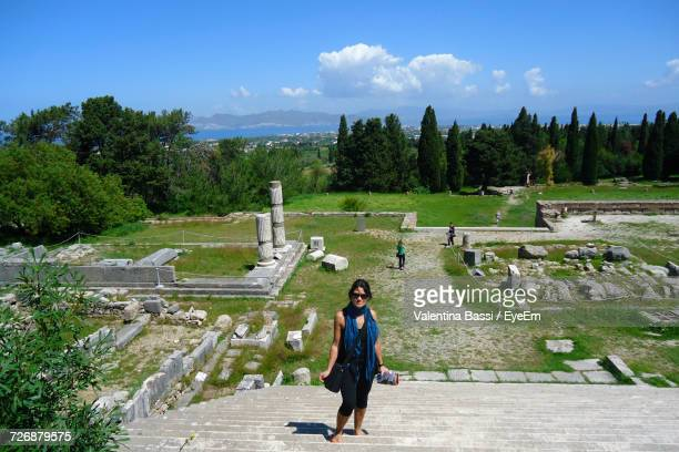 High Angle View Of Female Tourist Standing On Steps Against Old Ruins