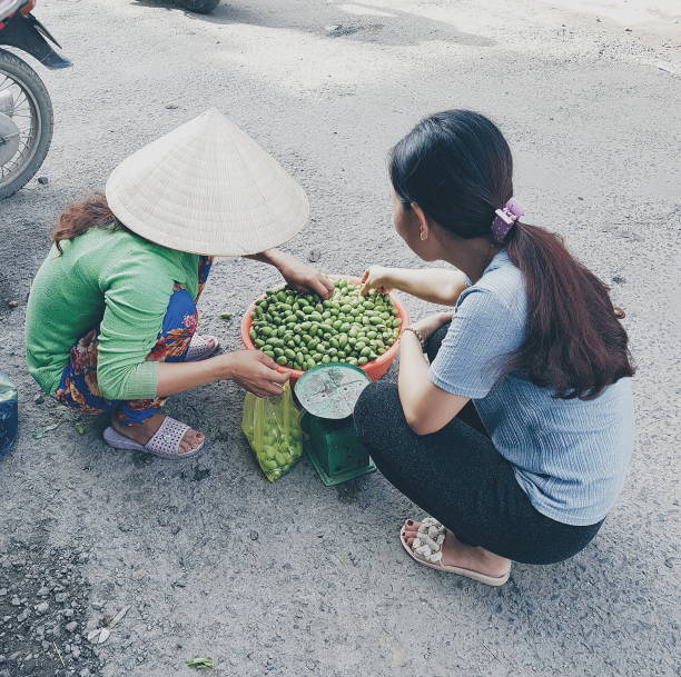 High Angle View Of Female Vendor Selling Food To Customer On Street