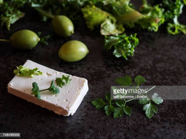 High Angle View Of Feta Cheese With Olives And Green Herbs On Marble Counter