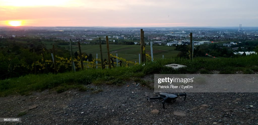 High Angle View Of Field By Buildings Against Sky During Sunset : Stock Photo