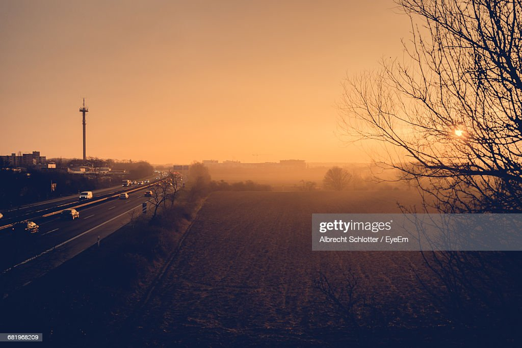 High Angle View Of Field By Highway Against Clear Sky During Sunrise : Stock-Foto