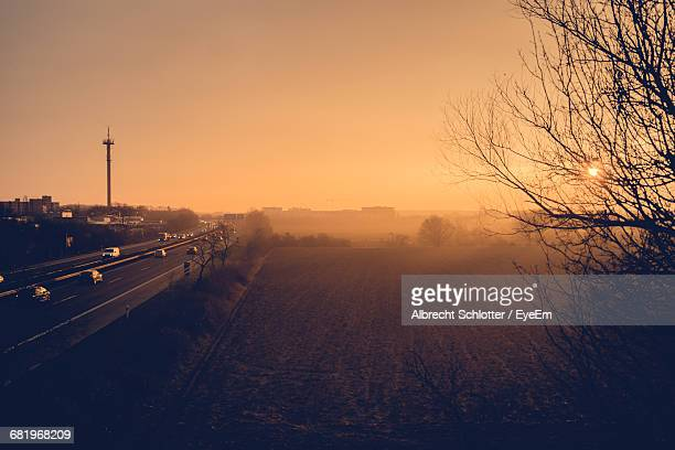 high angle view of field by highway against clear sky during sunrise - albrecht schlotter stock-fotos und bilder
