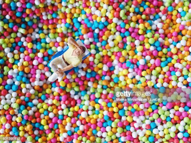 High Angle View Of Figurine On Multi Colored Balls