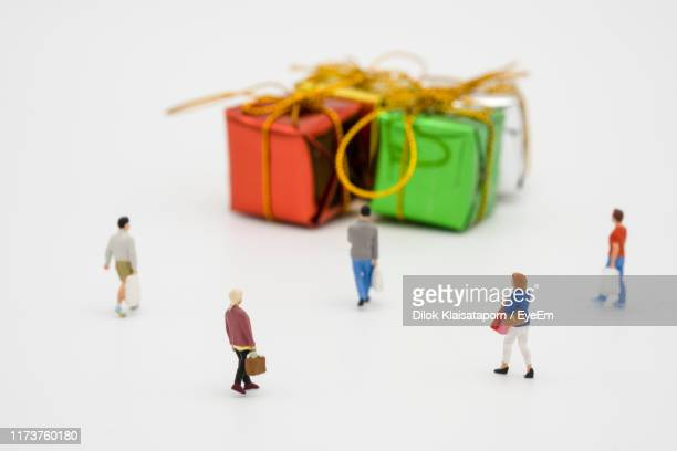 high angle view of figurines by gift boxes on white background - figurine stock pictures, royalty-free photos & images