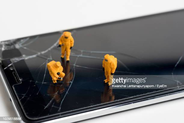 high angle view of figurines on broken mobile phone - craft product stock photos and pictures
