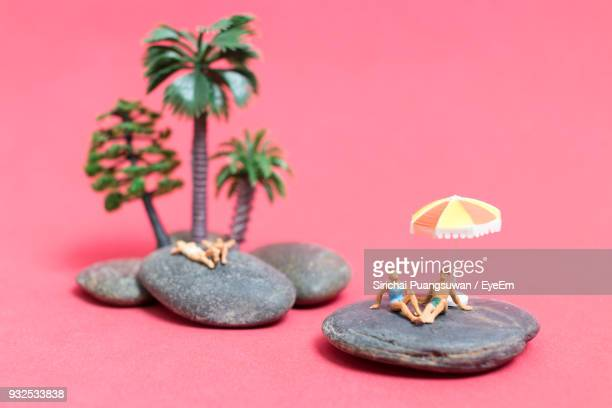 High Angle View Of Figurines On Stones By Toy Trees Over Peach Background