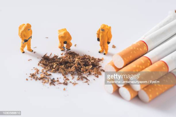 High Angle View Of Figurines With Cigarettes Over White Background