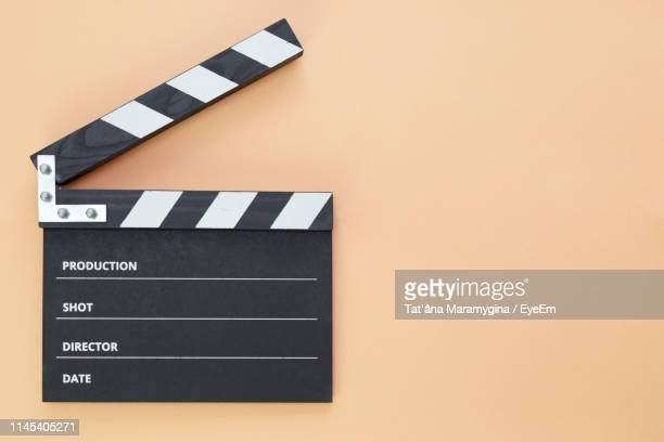 high angle view of film slate on beige background - clapboard stock pictures, royalty-free photos & images