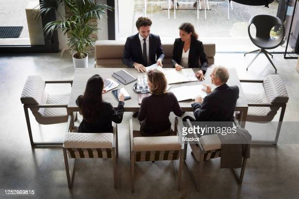 high angle view of financial advisors and customers discussing during meeting at law firm - legal system stock pictures, royalty-free photos & images
