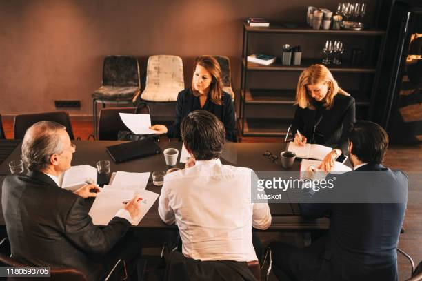 high angle view of financial advisors brainstorming in board room at office - cinco personas fotografías e imágenes de stock