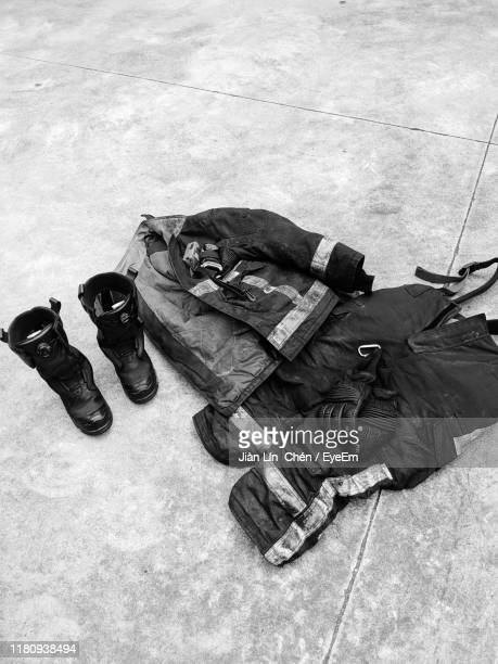 high angle view of fire protection suit on floor - fire protection suit stock pictures, royalty-free photos & images