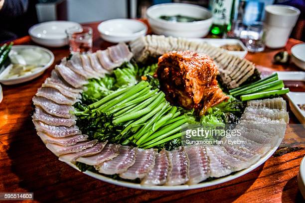 high angle view of fish and vegetables in plate on table - bucheon stock pictures, royalty-free photos & images