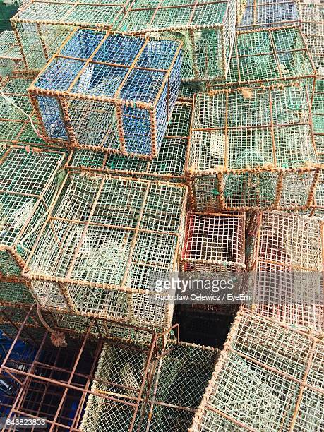 high angle view of fish trap stacked outdoors - crab pot stock photos and pictures