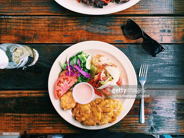 high angle view of fish with salad served in plate on table - puerto rico stock pictures, royalty-free photos & images