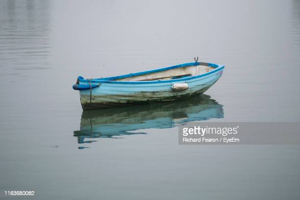 high angle view of fishing boat moored in lake - blue stock pictures, royalty-free photos & images