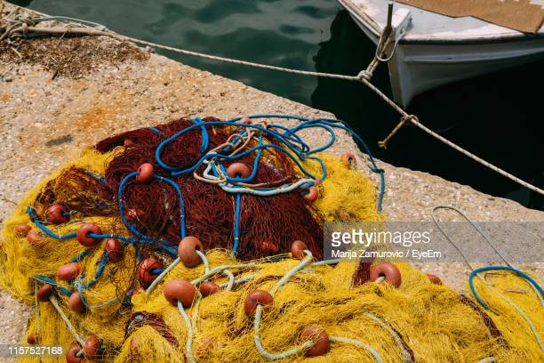 high angle view of fishing nets on retaining wall at harbor - marija mauer stock-fotos und bilder