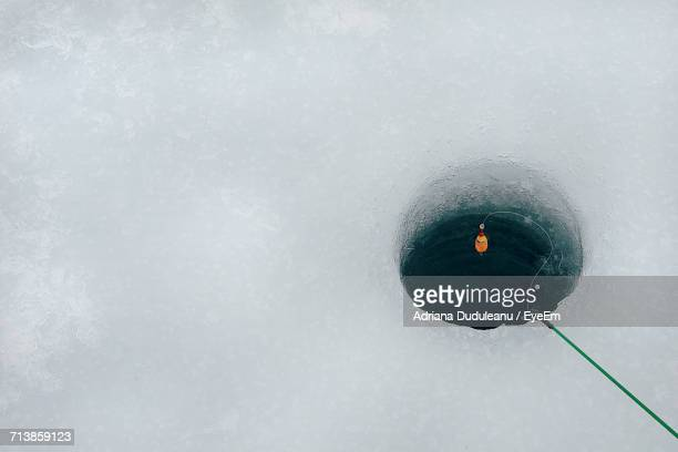 High Angle View Of Fishing Rod Over Hole In Frozen Lake