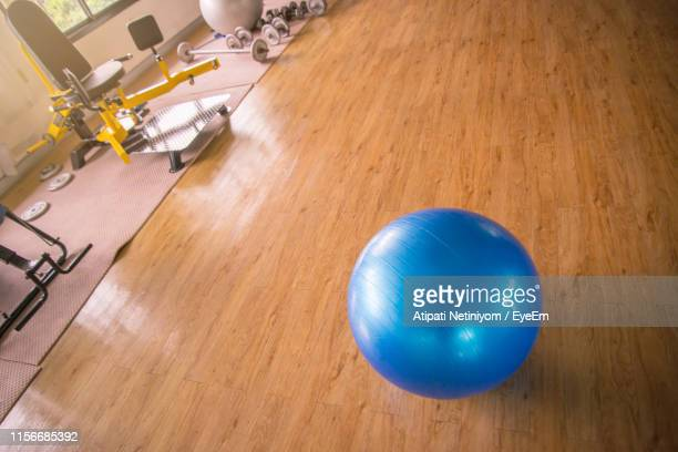 high angle view of fitness ball on hardwood floor in gym - fitness ball stock pictures, royalty-free photos & images