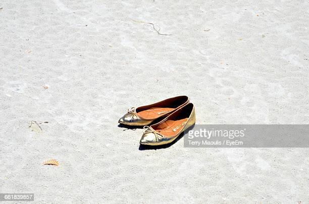 High Angle View Of Flat Shoes At Sandy Beach On Sunny Day