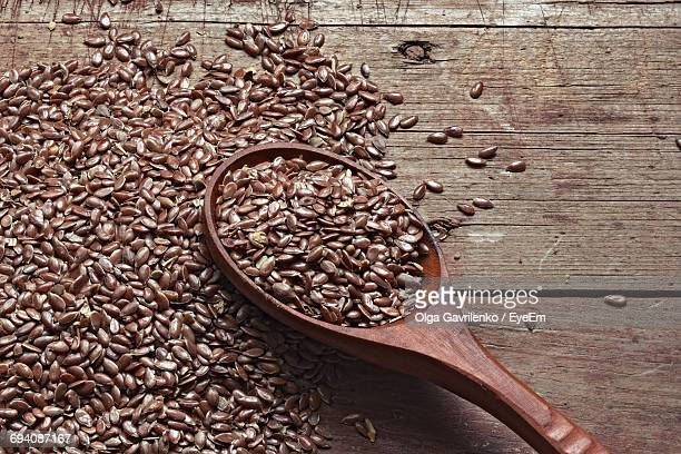 High Angle View Of Flax Seeds In Wooden Spoon On Table