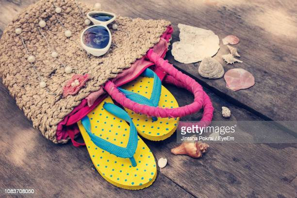 high angle view of flip-flops in bag by seashells on table - tote bag stock pictures, royalty-free photos & images