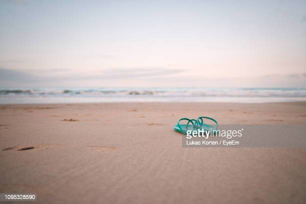 high angle view of flip-flops on beach against sea - flip flops stock pictures, royalty-free photos & images