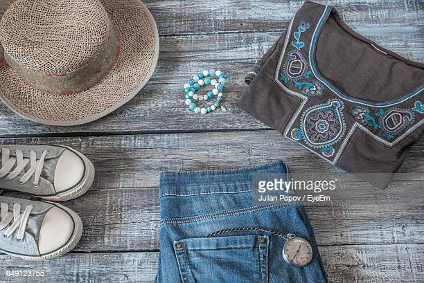 High Angle View Of Folded Dress By Wicker Hat With Canvas Shoes And Jeans On Wooden Floor