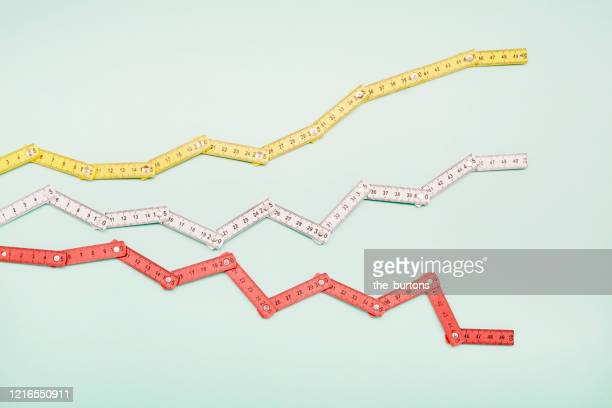 high angle view of folding rulers in shape of a stock curve on turquoise background - instrument of measurement stock pictures, royalty-free photos & images