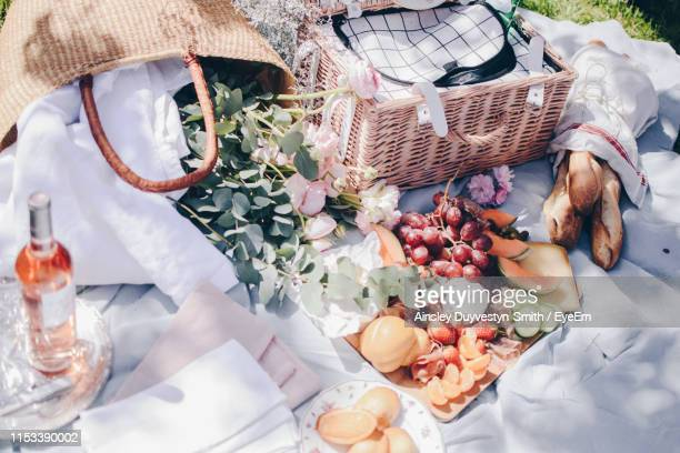 high angle view of food and basket on cloth - picknick stock-fotos und bilder
