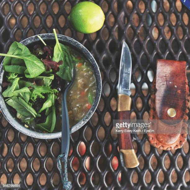 high angle view of food in bowl and knife on metal grate - kerry estey keith stock photos and pictures