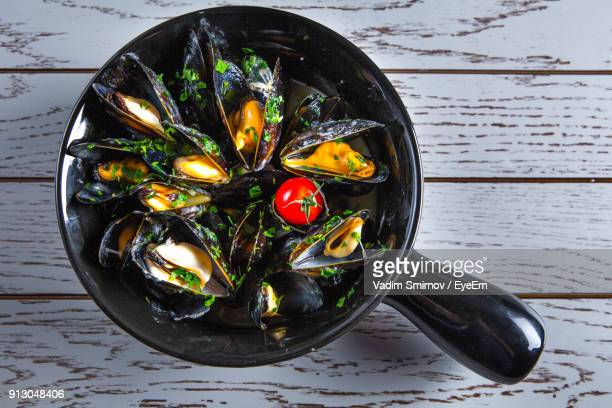 high angle view of food in cooking pan on table - mussel stock pictures, royalty-free photos & images