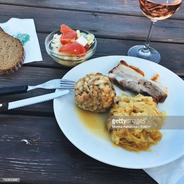 High Angle View Of Food In Plate And Drink On Wooden Table