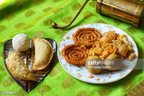 high angle view of food in plates on table - diwali stock photos and pictures