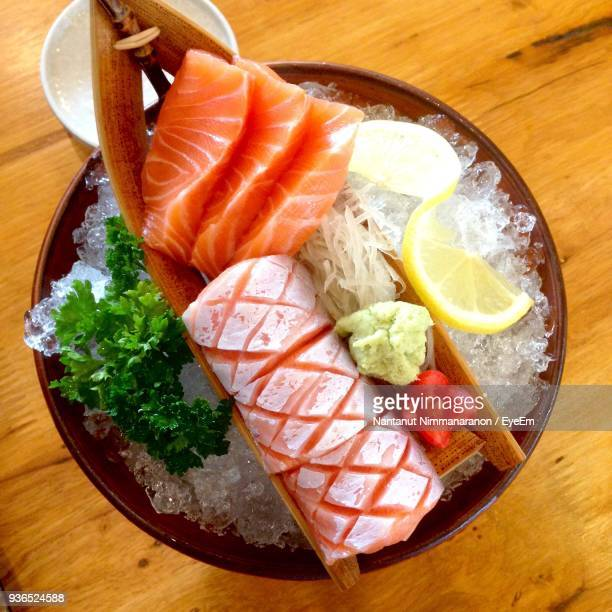 high angle view of food served in bowl on table - sashimi stock photos and pictures