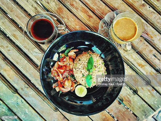 High Angle View Of Food Served In Plate By Drinks On Wooden Table