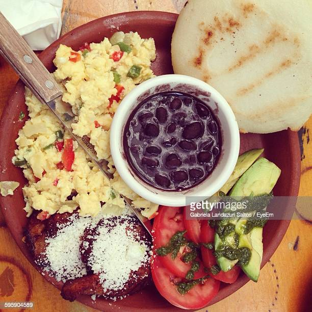 High Angle View Of Food Served In Plate With Arepa On Table