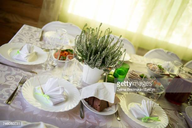 High Angle View Of Food With Drinking Glasses And Plates By Potted Plant On Table
