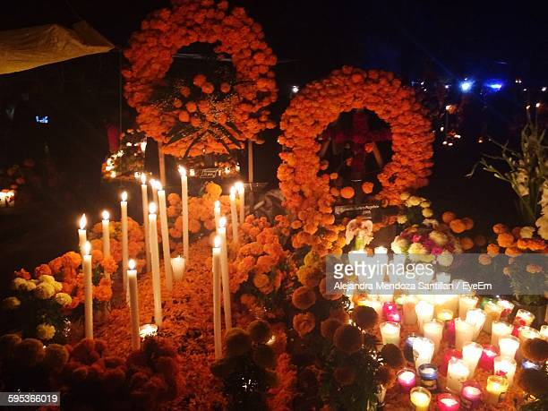 High Angle View Of Food With Illuminated Candles And Flowers During Day Of The Dead Festival