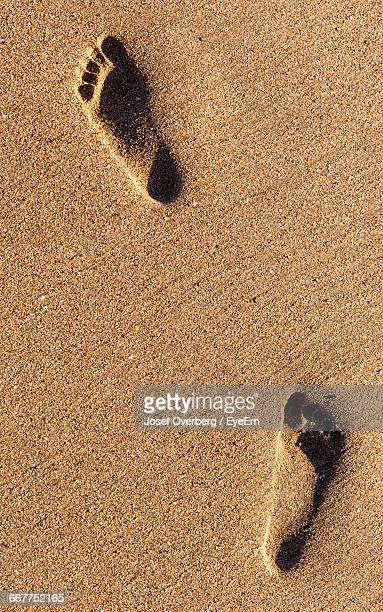 high angle view of footprints on sandy beach - overberg stock pictures, royalty-free photos & images